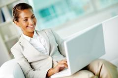 Portrait of smiling businesswoman with laptop in office Stock Photos