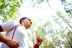 image of young sportsman with earphones running in park - stock photo