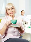 Portrait of mature woman with cup looking at camera on background of her husband Stock Photos