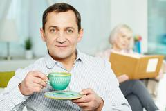 Portrait of happy senior man with cup and his wife reading book behind Stock Photos