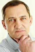 face of mature man touching his chin and looking at camera - stock photo