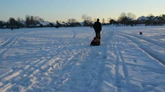 Man father pull sledge with little kid child son and people walk Stock Footage