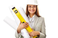 portrait of smiling businesswoman in helmet holding rolled blueprints - stock photo