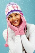 portrait of pretty woman in pink gloves and knitted winter cap looking at camera - stock photo
