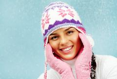 Face of pretty woman in pink gloves and knitted winter cap looking at camera wit Stock Photos