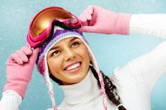 Pretty woman in goggles and knitted winter cap looking upwards with smile Stock Photos