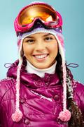 pretty woman in goggles and winter clothes looking at camera with smile - stock photo