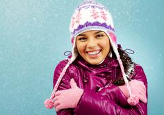 smiling girl looking at camera showing how cold she is - stock photo