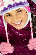 pretty woman in winter clothes looking at camera with smile - stock photo
