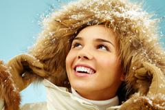 Stock Photo of happy woman with furry hood on head in good mood
