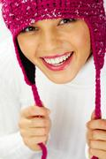 portrait of cheerful woman in knitted winter cap looking at camera with smile - stock photo