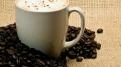Cup of cappuccino with roasted coffee beans Stock Footage