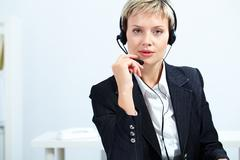 portrait of customer service operator with headset looking at camera - stock photo