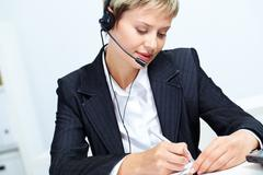 portrait of young secretary with headset making notes - stock photo
