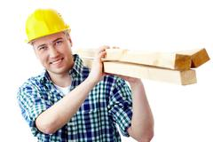 Portrait of a cheerful worker in helmet carrying lumber Stock Photos