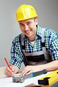 Stock Photo of portrait of a smiling architect making corrections on a plan