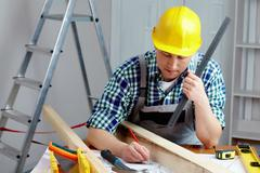 Stock Photo of a young repairmen sitting at table and working with a plan