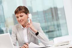 Photo of smart businesswoman calling and smiling in office Stock Photos