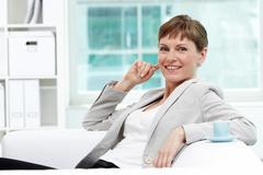 portrait of smiling businesswoman looking at camera in office - stock photo