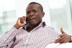 Image of handsome businessman or agent talking by cellular phone Stock Photos