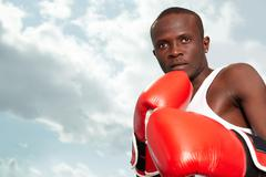 Image of a boxer in red gloves against cloudy sky Stock Photos