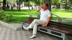 Businessman on a bench calling at the cellular on beautidul grass background Stock Footage