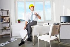 Portrait of architect in helmet drinking tea in office Stock Photos