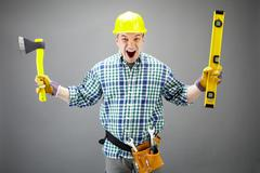 portrait of crazy architect worker with axe and level measuring device - stock photo
