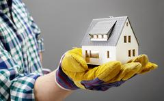 Gloved hand of architect holding a house model Stock Photos