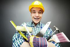 Portrait of happy craftsman with different tools in hands Stock Photos