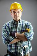 portrait of confident worker in helmet isolated on grey - stock photo