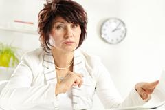 portrait of middle-aged female at workplace looking at camera - stock photo