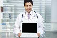 portrait of happy doctor with open laptop looking at camera - stock photo
