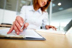 Human hand with pen over paper during work in office Stock Photos