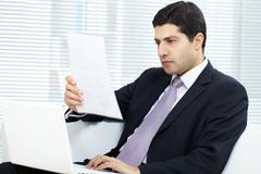 Portrait of attractive businessman in suit working in office Stock Photos