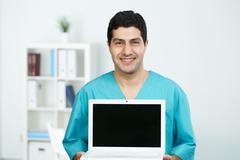portrait of happy surgeon with open laptop looking at camera - stock photo
