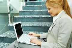 Image of businesswoman with laptop working on staircase Stock Photos