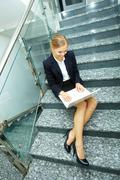 Image of smart businesswoman with laptop working on staircase Stock Photos