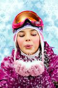 Portrait of a girl blowing snow out of hands against a drawn background Stock Photos