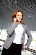 portrait of smiling businesswoman talking on cellular phone - stock photo