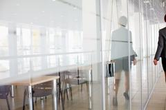 Reflection of businesswoman walking along the office corridor Stock Photos