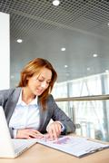 portrait of successful businesswoman working with documents in office - stock photo