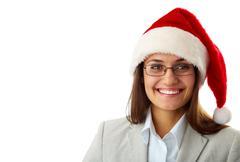 Portrait of happy businesswoman in santa cap smiling at camera Stock Photos