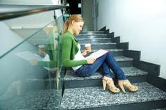 Photo of pretty girl with coffee reading paper on stairs of college Stock Photos