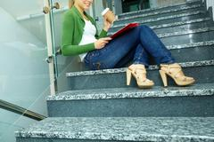 photo of student with coffee sitting on stairs of college - stock photo