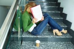 Photo of pretty student hiding her face behind paper on stairs of college Stock Photos