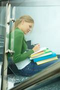 image of pretty girl sitting on stairs and making notes in copybook - stock photo