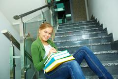 Image of pretty girl with books looking at camera in college Stock Photos