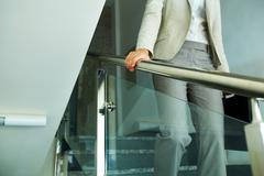 Close-up of businesswoman with briefcase going down the stairway Stock Photos