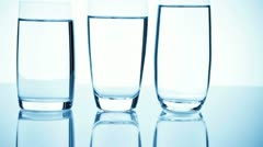 Three different glasses filled with water showing reflections Stock Footage